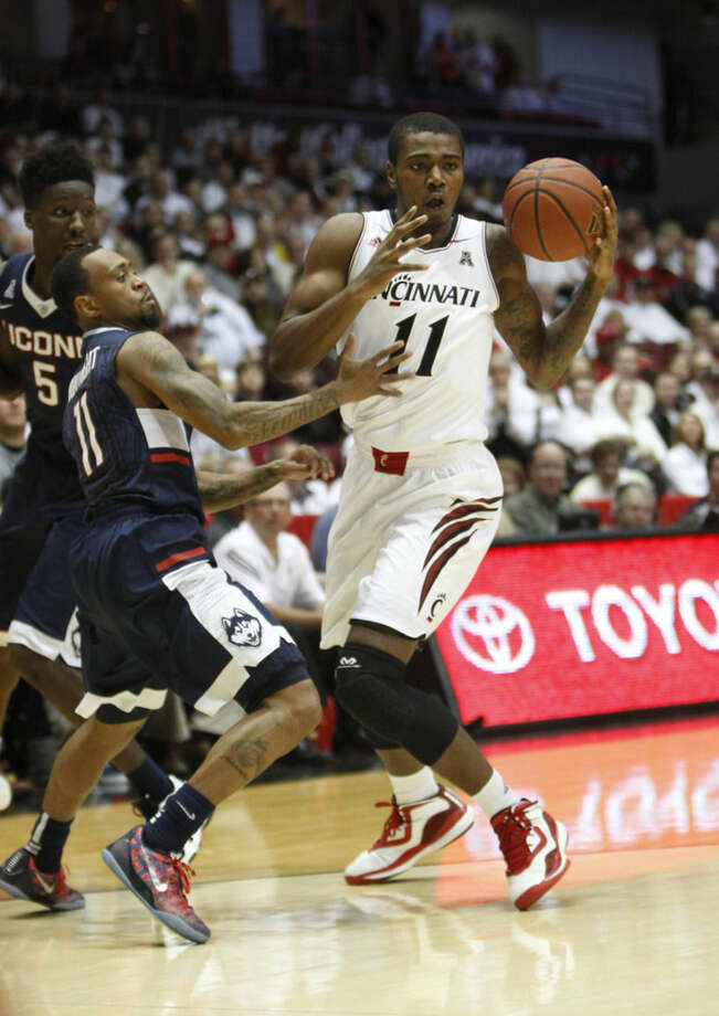 Cincinnati forward Gary Clark (11) protects the ball against UConn guard Ryan Boatright (11) in the first half of an NCAA college basketball game, Thursday, Jan. 29, 2015, in Cincinnati. (AP Photo/Frank Victores)