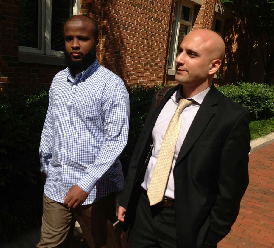 """FILE - In this Aug. 16, 2013, file photo, Gulet Mohamed, left, leaves the federal court in Alexandria, Va., with his attorney, Gadeir Abbas, with the Council on American-Islamic Relations, after a hearing challenging his placement on the government's no fly list. The FBI on Jan. 29, 2015, added Liban Haji Mohamed, a former taxi driver from northern Virginia to its list of most wanted terrorists, saying he was a recruiter for the al-Shabab terror group in Somalia. An arrest warrant, originally issued in February, was unsealed in U.S. District Court in Alexandria for Liban Haji Mohamed, 29, a naturalized U.S. citizen born in Somalia. The family denies that Mohamed committed any wrongdoing and suspects he went into hiding to avoid constant harassment from the FBI. """"Al-Shabab has killed Liban's uncle and imprisoned his cousins,"""" said Abbas, who for years has represented Mohamed's brother in a civil-rights suit against the government. """"His family believes the allegations have no basis in fact."""" (AP Photo/Matthew Barakat, File)"""