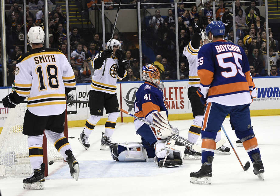 Boston Bruins right wing Reilly Smith (18) and left wing Loui Eriksson, left, rear, celebrate center Patrice Bergeron's goal as New York Islanders goalie Jaroslav Halak (41) and defenseman Johnny Boychuk (55) react in the first period of an NHL hockey game at Nassau Coliseum on Thursday, Jan. 29, 2015, in Uniondale, N.Y. (AP Photo/Kathy Kmonicek)