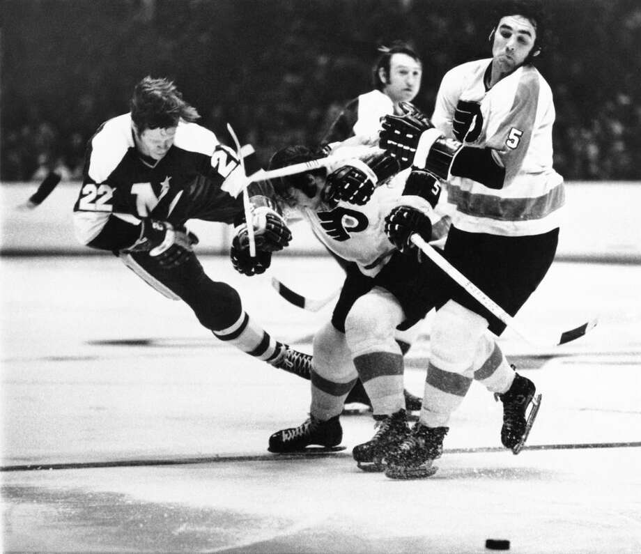 FILE - In this March 2 1972, file photo, Minnesota North Stars' Dennis Hextall (22) flips over the back of Philadelphia Flyers Bill Brossart , center, during the first period of an NHL hockey game in Philadelphia. Fifty years ago this week, the owners of the so-called Original Six unanimously approved doubling in size by awarding franchises to Los Angeles, San Francisco/Oakland, Philadelphia, Pittsburgh, St. Louis and Minneapolis/St. Paul. No other pro sports league had ever doubled its amount of teams, but the gamble proved to be one of the most important decisions in hockey history. (AP Photo/File)