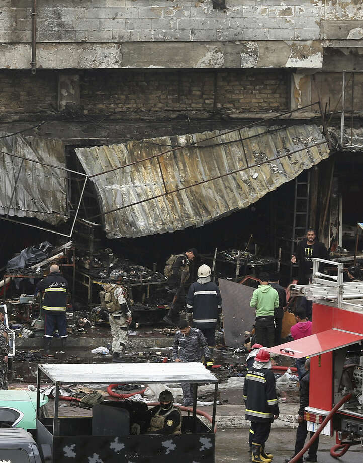 Security forces inspect the site of a twin bombing at a crowded market in Baghdad Iraq, Friday, Jan. 30, 2015. Police officials say the Friday morning attack started with a bomb exploding near carts selling used clothes in the city's central Bab al-Sharqi area. The second explosion, caused by a car bomb, went off two minutes later targeting people who rushed to help the victims from the first blast, killed and wounded more than a dozen of people, Iraqi officials said. (AP Photo/Hadi Mizban)