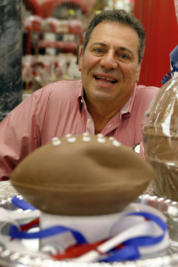 """Bill Sarris, the owner of Sarris Candy, poses behind the """"deflated"""" chocolate football called a """"Bradie"""" Ball at Sarris Candy store in in Canonsburg, Pa., on Wednesday, Jan. 28, 2015. Sarris says they came up with the idea to poke fun at the controversy surrounding under-inflated footballs on Tuesday. The display item isn't for sale. (AP Photo/Keith Srakocic)"""