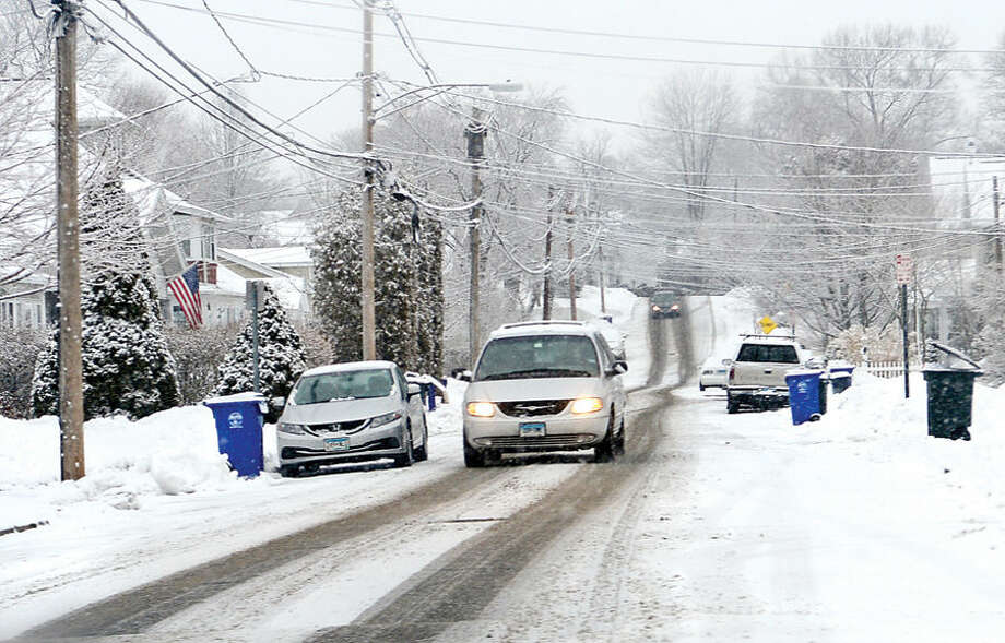 Hour photo / Erik Trautmann sideroads remain slippery during a light snowfall Friday morning that caused delayed openings for Norwalk Public Schools.