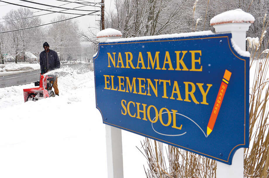 Hour photo / Erik Trautmann Norwalk Recreation and Parks employee Marvin Sanders cleans up after a light snowfall Friday morning that caused delayed openings for Norwalk Public Schools.