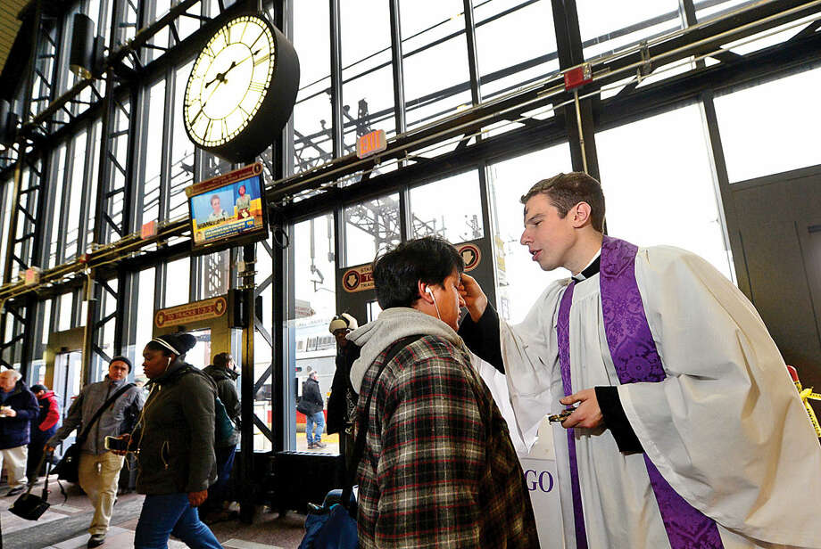 Hour photo / Erik Trautmann St. Paul's on the Green Reverend Peter Thompson offers Ashes-to-Go to Pablo Perez at the South Norwalk train station on Wednesday morning. This was the first year that St. Paul's took part in the 9 year old Episcopal Church's Ashes-to-Go tradition.