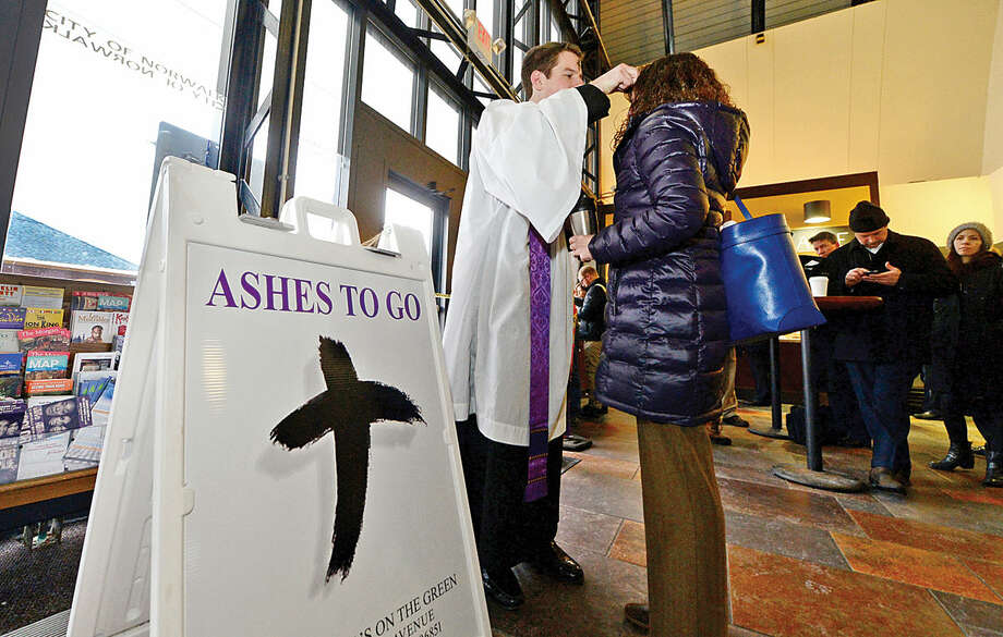 Hour photo / Erik Trautmann St. Paul's on the Green Reverend Peter Thompson offers Ashes-to-Go to Maureen Pudelka at the South Norwalk train station on Wednesday morning. This was the first year that St. Paul's took part in the 9 year old Episcopal Church's Ashes-to-Go tradition.
