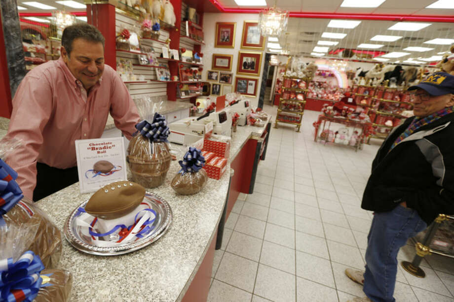 """Bill Sarris, the owner of Sarris Candy, left, and a passing customer look down at the """"deflated"""" chocolate football called a """"Bradie"""" Ball at Sarris Candy store in in Canonsburg, Pa., on Wednesday, Jan. 28, 2015. Sarris says they came up with the idea to poke fun at the controversy surrounding under-inflated footballs on Tuesday. The display item isn't for sale. (AP Photo/Keith Srakocic)"""