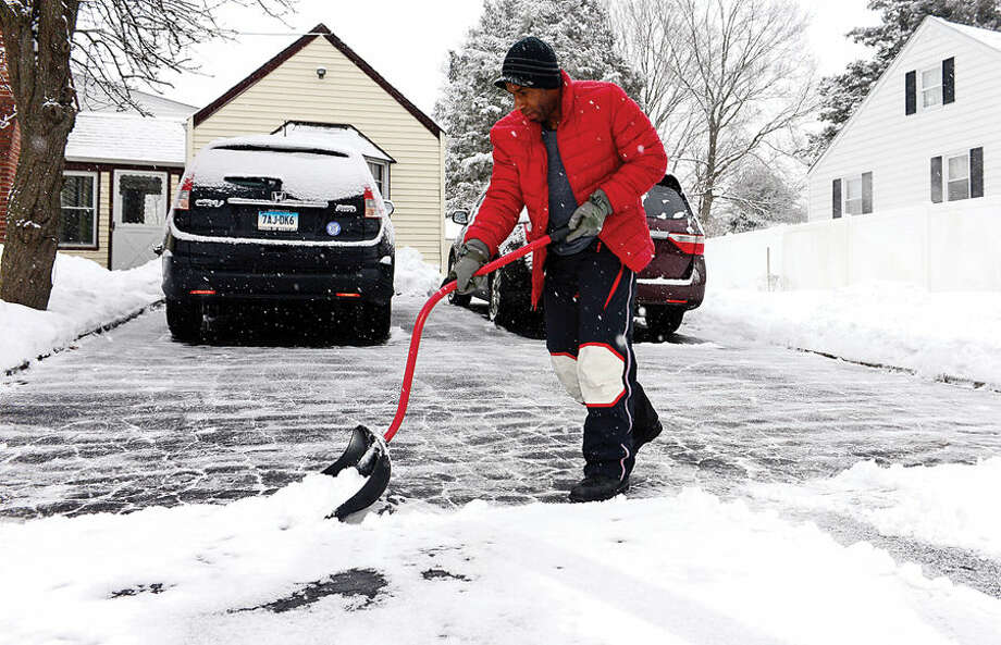 Hour photo / Erik Trautmann Geral Miles cleans up during a light snowfall at his home on Williams St Friday morning. The snow caused a 2 hour delay in opening of local schools.