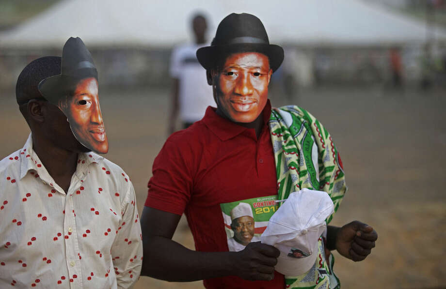 Supporters of Nigerian President Goodluck Jonathan, wear masks depicting his face during his visit in Yola, Nigeria, Thursday, Jan. 29, 2015. Youths angry at the Nigerian government's failure to fight Islamic extremists threw stones Thursday at President Goodluck Jonathan's electioneering convoy in the eastern town of Jalingo, breaking windshields and windows on several vehicles. (AP Photo/Lekan Oyekanmi)
