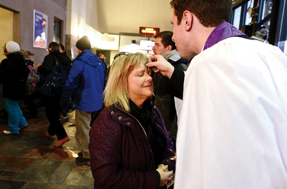 Hour photo / Erik Trautmann St. Paul's on the Green Reverend Peter Thompson offers Ashes-to-Go to commuters at the South Norwalk train station on Wednesday morning. Thiis was the first year that St. Paul's took part in the 9 year old Episcopal Ashes-to-Go tradition.