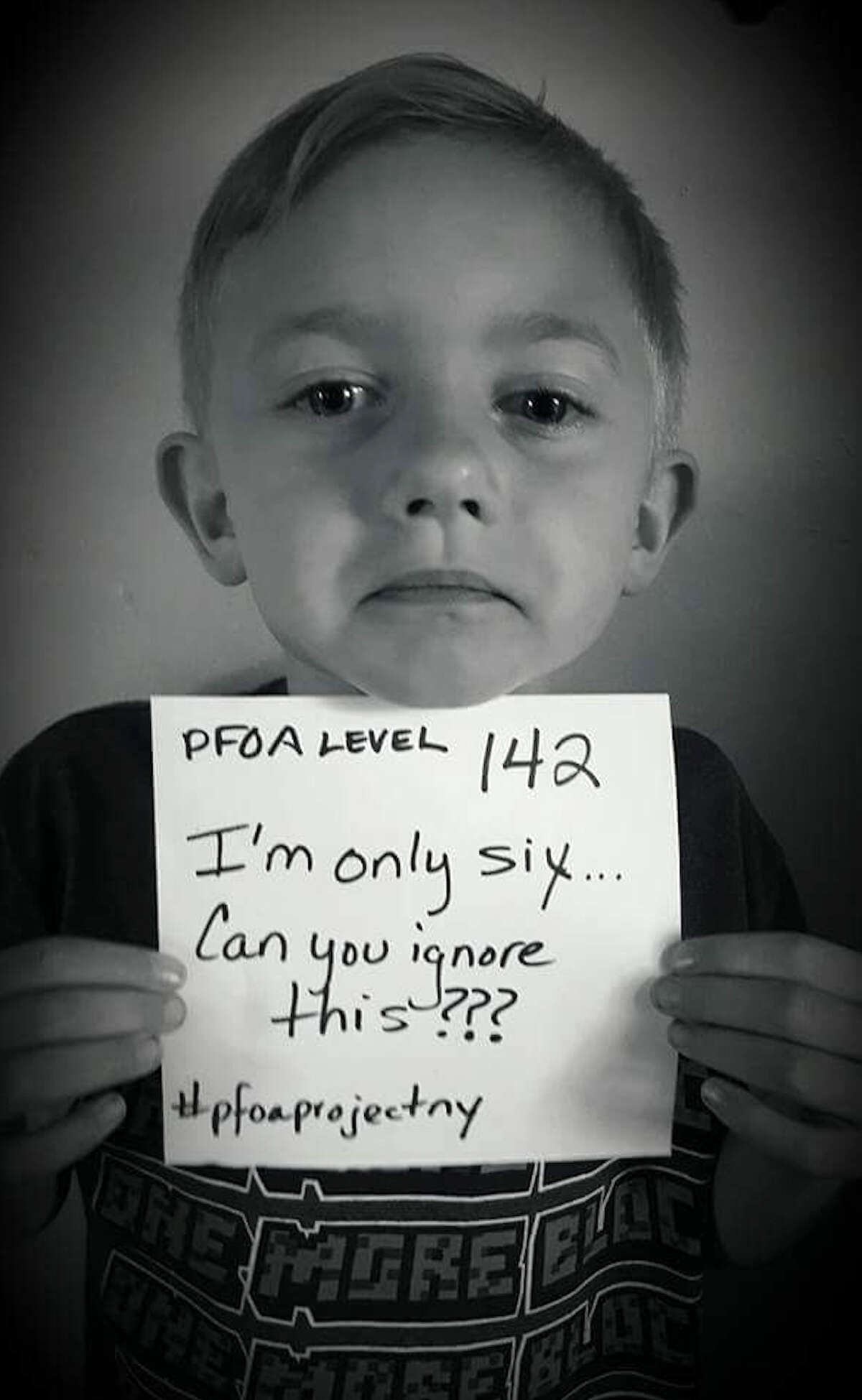 Hoosick Falls resident, Corey Aldrich, 6, displays a sign with his body's PFOA level after receiving the results of a recent blood test conducted by the state. The photo was posted on Twitter by parents, Josh and Nikki Aldrich. (Courtesy Josh and Nikki Aldrich)