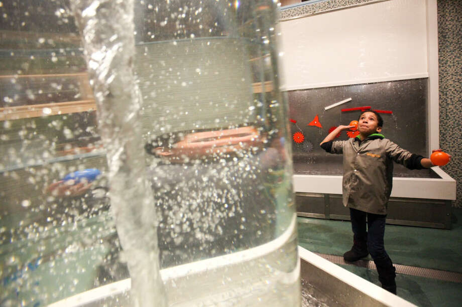 Hour photo/Chris Palermo Kids throw balls into the cyclone at the Norwalk Mentor Program's annual mentor/mentee event at Stepping Stones Museum Thursday night.