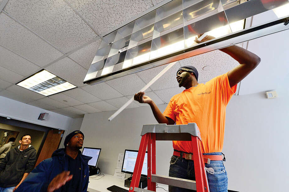 Hour photo / Erik Trautmann Michael Thompson and Andre Campbell of Taylor electric install energy efficient upgrades to light fixtures at Norwalk City Hall Friday following a press conference by Norwalk Mayor Harry Rilling and Councilman John Kydes who announced the upgrades.