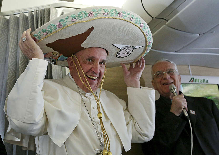 Pope Francis wears a traditional Mexican sombrero hat he received as a gift by a Mexican journalist aboard the plane during the flight from Rome to Habana, Cuba, on his way to a week-long trip to Mexico, Friday, Feb. 12, 2016. The pontiff is scheduled to stop in Cuba for an historical meeting with Russian Orthodox Patriarch Kirill that the Vatican sees as a historic step in the path toward healing the 1,000-year schism that split Christianity. At right is Vatican spokesperson Rev. Federico Lombardi. (Alessandro Di Meo/Pool Photo via AP)