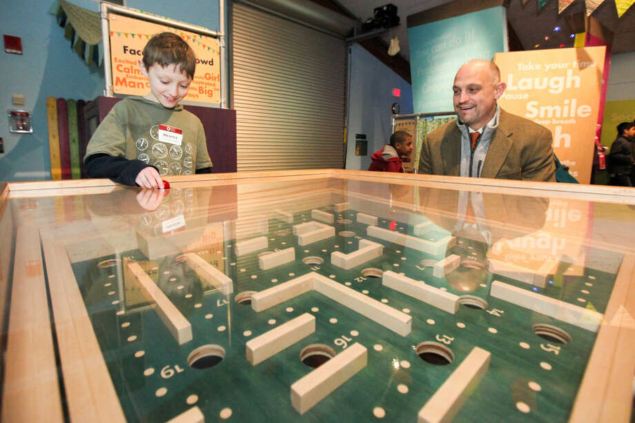 Hour photo/Chris Palermo Raleigh Fiore, 9, plays the labyrinth game with his father Frank at the Norwalk Mentor Program's annual mentor/mentee event at Stepping Stones Museum Thursday night.
