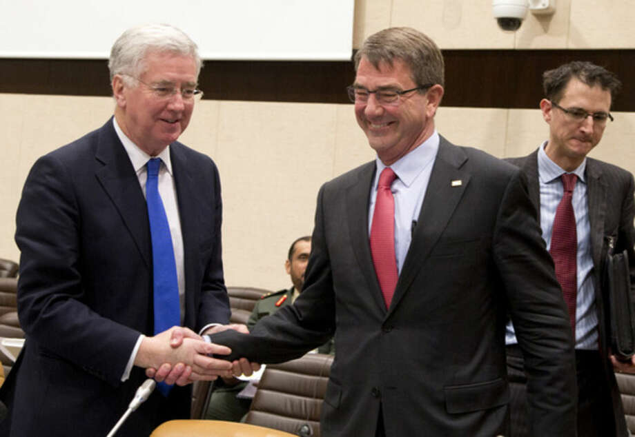 U.S. Secretary of Defense Ash Carter, second right, shakes hands with British Secretary of State for Defense Michael Fallon during a Counter-ISIL Coalition Ministerial meeting at NATO headquarters in Brussels on Thursday, Feb. 11, 2016. U.S. Defense Secretary Ash Carter expects Thursday's three-hour gathering of defense ministers from more than two dozen countries to endorse a new U.S. plan for prosecuting the war. The ministers were expected to issue a joint statement at the conclusion of their meeting at NATO headquarters. (AP Photo/Virginia Mayo)
