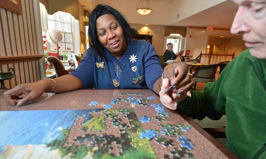 Certified Nursing Assistant Joan Grant works on a puzzle with one of the guests at The Greens at Cannondale.