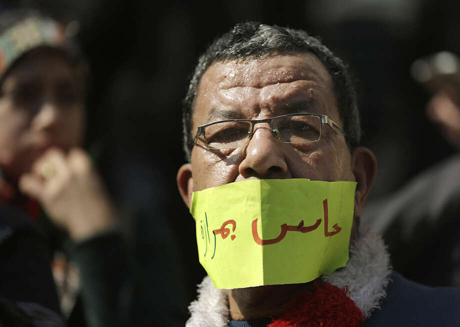 "An Egyptian doctor covers his mouth with a paper reading,""I feel painful,"" during a protest against rampant police abuses, after two doctors were beaten up by policemen in a Cairo hospital, in front of their headquarters of the Egyptian Medical Syndicate in Cairo, Egypt, Friday, Feb. 12, 2016. Doctors threatened to escalate if the government doesn't hold police accountable for abuses. Attendees chanted ""strike"" and raised banners read, ""Doctors' Dignity."" (AP Photo/Amr Nabil)"