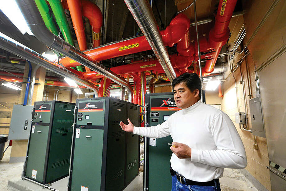Hour photo / Erik Trautmann Alan Lo, Building and Facilities Manager at City of Norwalk, leads a tour of the energy efficient upgrades to Norwalk City Hall including three new boilers Friday following a press conference by Mayor Harry Rilling and Councilman John Kydes who announced the upgrades.