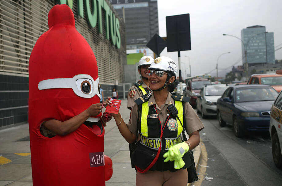 A man dressed as a condom hands out a box of condoms to a traffic police officer during International Condom Day in Lima, Peru, Friday, Feb. 12, 2016. During the day health workers will hand out informational material to promote condom use and offer AIDS awareness-raising activities. The event will also offer free rapid HIV testing. (AP Photo/Martin Mejia)