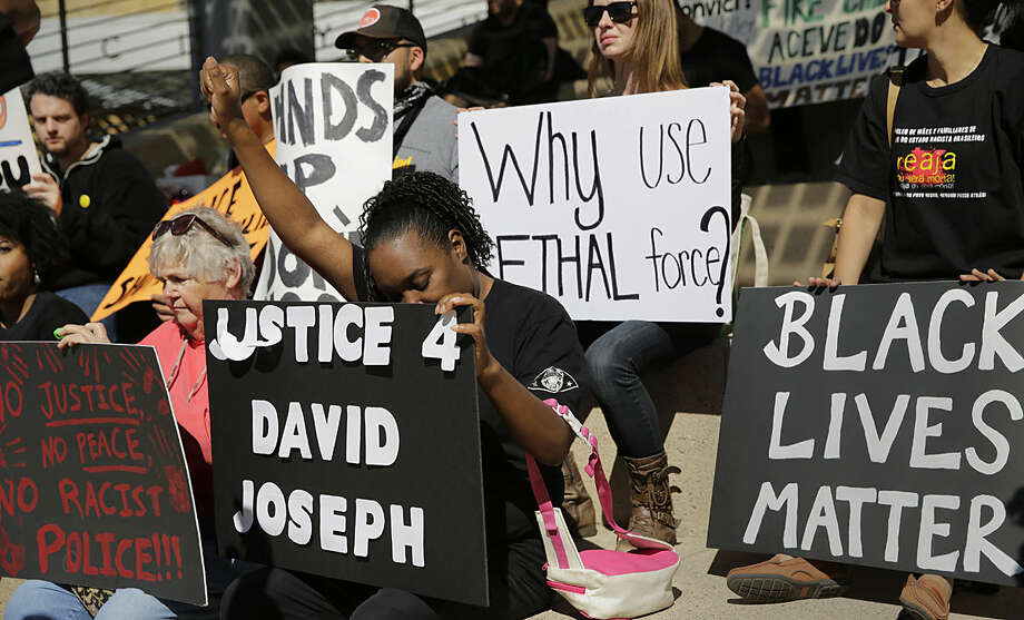 Juanita Spears, center, raises her hand during a rally at Austin City Hall in response to the recent fatal police shooting of David Joseph, 17, Thursday, Feb. 11, 2016, in Austin, Texas. The shooting of Joseph, who was naked and unarmed, has provoked outcry among social justice activist groups. (AP Photo/Eric Gay)