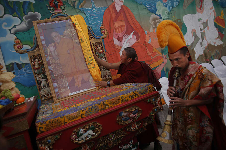 "A Tibetan monk places a portrait of Tibetan spiritual leader, the Dalai Lama, on a raised platform during a special prayer ceremony on the third day of the Tibetan New Year celebrations in Kathmandu, Nepal, Thursday, Feb. 11, 2016. Tibetans follow this ritual called ""sangtsol"" to ask for good luck in the new year. (AP Photo/Niranjan Shrestha)"