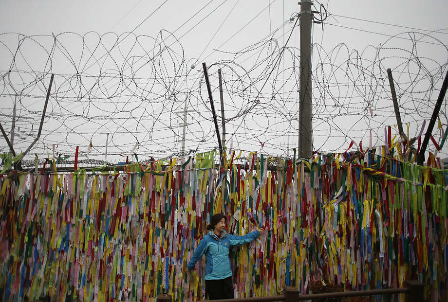 A woman poses for a souvenir photo in front of ribbons hanging on a wire fence for the reunification of the two Koreas at the Imjingak Pavilion near the border village of Panmunjom in Paju, South Korea, Friday, Feb. 12, 2016. South Korea has cut off power and water supplies to a factory park in North Korea, officials said Friday, a day after the North deported all South Korean workers there and ordered a military takeover of the complex that had been the last major symbol of cooperation between the rivals. (AP Photo/Lee Jin-man)