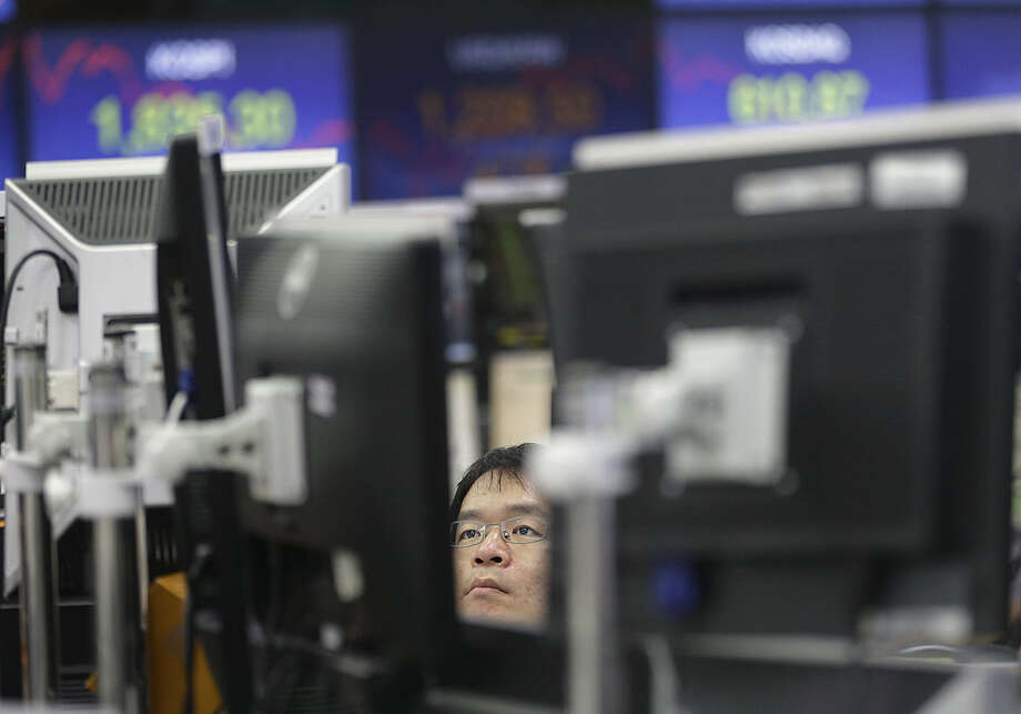 A currency trader watches monitors at the foreign exchange dealing room of the KEB Hana Bank headquarters in Seoul, South Korea, Friday, Feb. 12, 2016. Japan's main stock index dived Friday, leading other Asian markets lower, after a sell-off in banking shares roiled investors in the U.S. and Europe. (AP Photo/Ahn Young-joon)