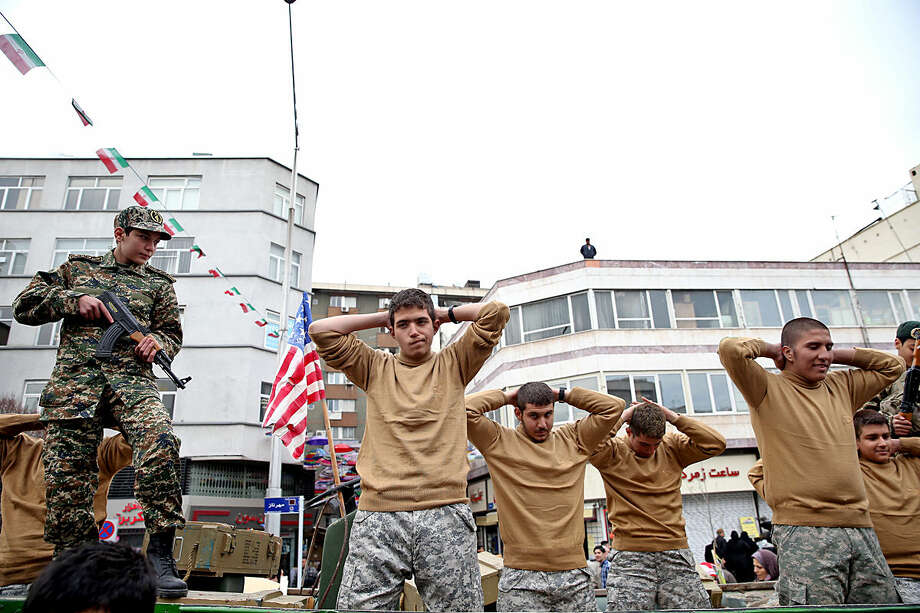 Members of Iranian Basij paramilitary force re-enact the January capture of U.S sailors by the Revolutionary Guard in the Persian Gulf, in a rally commemorating the 37th anniversary of Islamic Revolution in Tehran, Iran, Thursday, Feb. 11, 2016. The nationwide rallies commemorate Feb. 11, 1979, when followers of Ayatollah Khomeini ousted U.S.-backed Shah Mohammad Reza Pahlavi. (AP Photo/Ebrahim Noroozi)