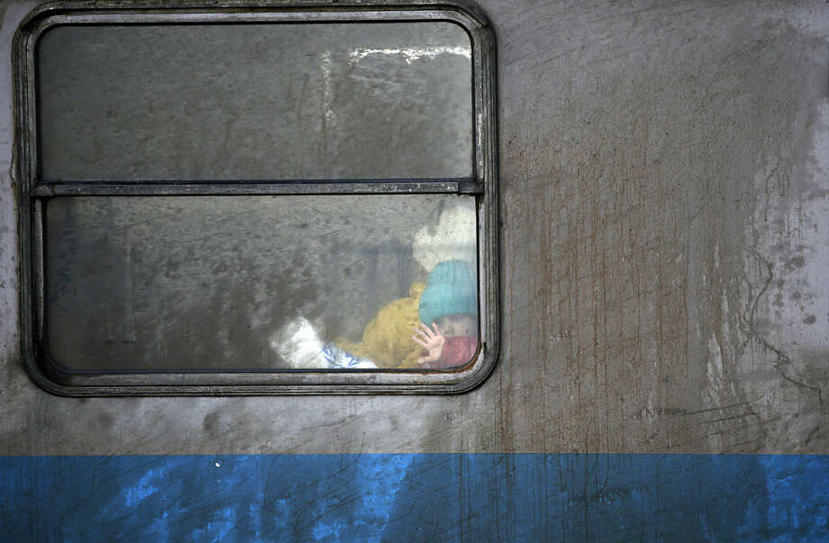 A migrant child waves through a train window waiting to leave toward Croatia from the Serbian border town of Sid, about 100 km (62 miles) west from Belgrade, Friday, Feb. 12, 2016. Sen. McCain and a U.S. Congress delegation pledged assistance to Serbia and other countries along the Balkan migrant route. (AP Photo/Darko Vojinovic)