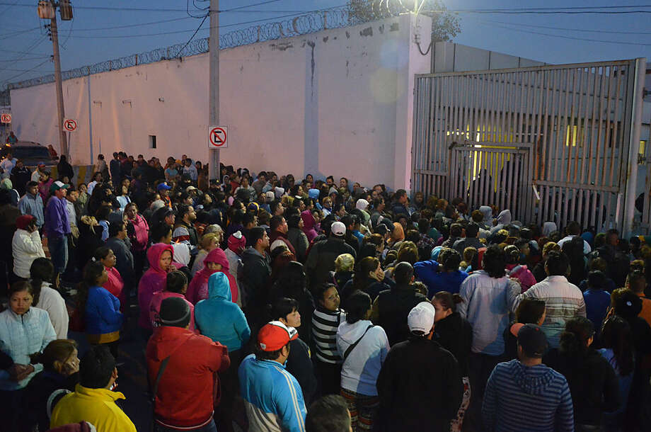 Relatives of inmates stand outside the Topo Chico prison, where a riot broke out around midnight, in Monterrey, Mexico, Thursday, Feb. 11, 2016. Dozens of inmates were killed and several injured in a brutal fight between two rival factions at the prison in northern Mexico, the state governor said. (AP Photo/Emilio Vazquez)