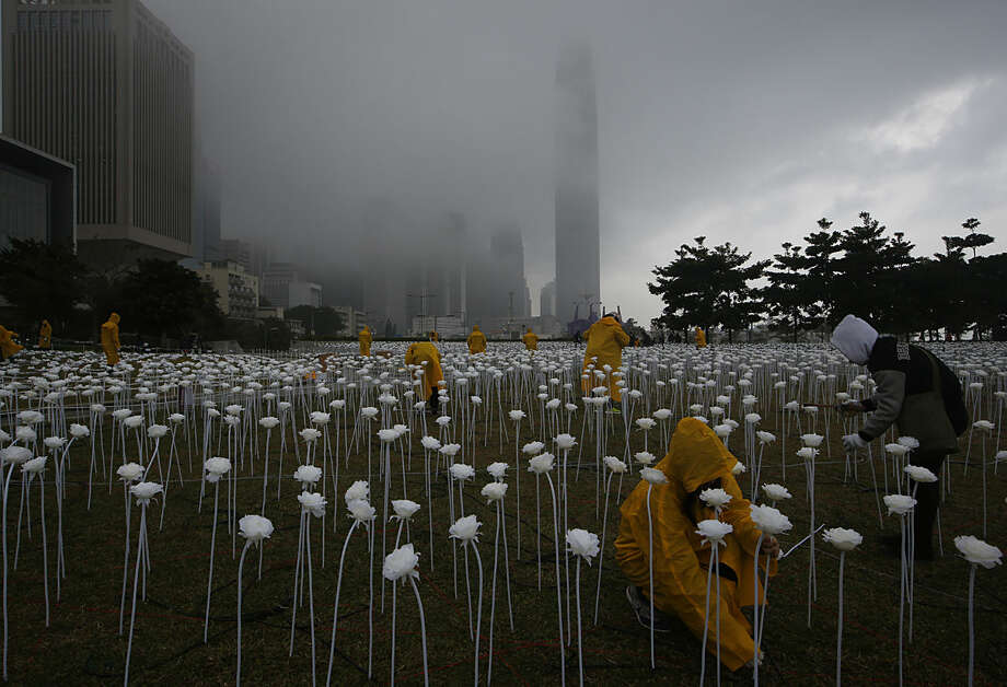 "Workers place LED roses at the ""Light Rose Garden"", against the backdrop of Central, the business district of Hong Kong, Friday, Feb. 12, 2016. ""Light Rose Garden"" is an art installation project featuring 25,000 white roses made of LED lights which will light up for the celebration of the Valentine's Day. (AP Photo/Kin Cheung)"