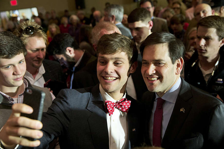 Wearing a bowtie with U.S. flags on it, Southside Christian High School senior Parker Stewart, 18, talks a selfie on his cellphone with Republican presidential candidate Sen. Marco Rubio, R-Fla., after a town hall meeting at the school in Simpsonville, S.C., Thursday Feb. 11, 2016. (AP Photo/Jacquelyn Martin)