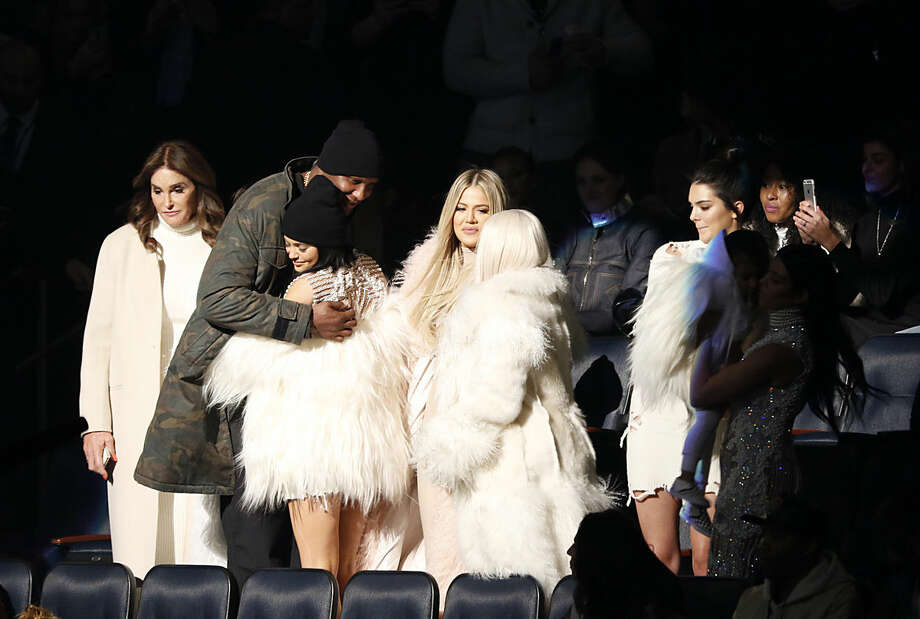 """Lamar Odom, second left, hugs Kylie Jenner as Caitlyn Jenner, left, Khloe Kardashian Odom, center, Kim Kardashian, Kendall Jenner, North West and Kourtney Kardashian (both out of spotlight) attend the unveiling of the Yeezy collection and album release for Kanye West's latest album, """"The Life of Pablo,"""" Thursday, Feb. 11, 2016 at Madison Square Garden in New York. (AP Photo/Bruce Barton)"""