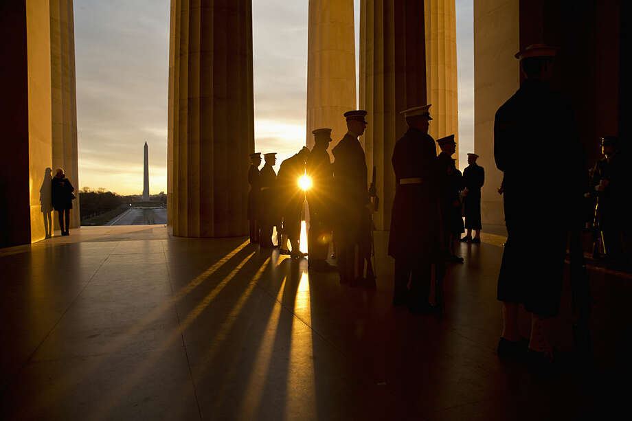 As the sun rises, military personnel practice their positioning during a rehearsal before a Presidential Full Honor Wreath-Laying Ceremony in celebration of the 207th birthday of President Abraham Lincoln, Friday, Feb. 12, 2016, at the Lincoln Memorial Washington. (AP Photo/Alex Brandon)