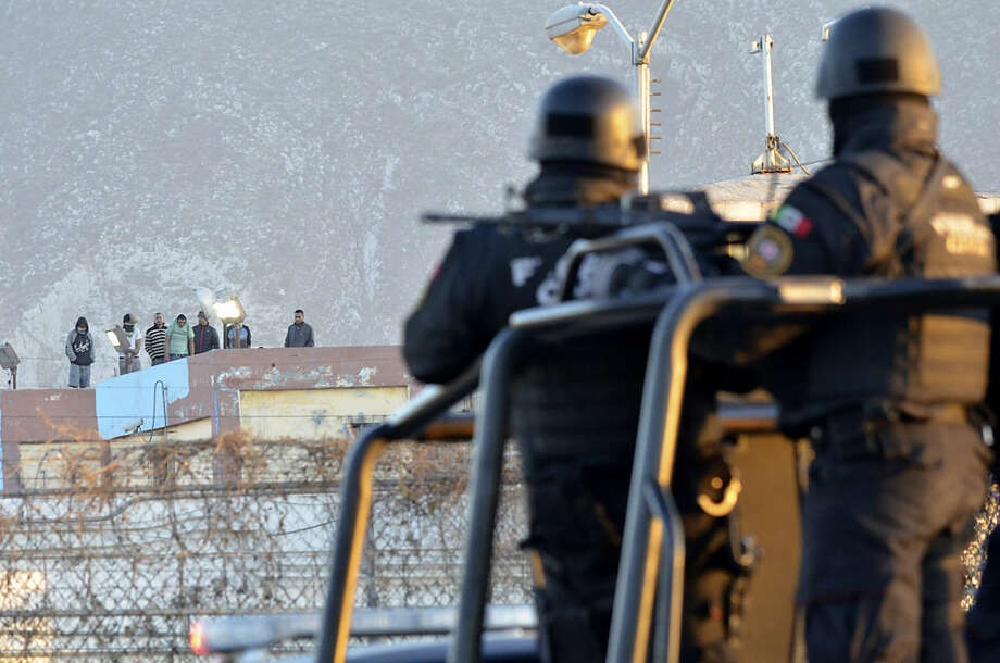 Inmates stand on the rooftop of the Topo Chico prison as police stand guard on the perimeters, after a riot broke out around midnight, in Monterrey, Mexico, Thursday, Feb. 11, 2016. Dozens of inmates were killed and several injured in a brutal fight between two rival factions at the prison in northern Mexico, the state governor said. (AP Photo/Emilio Vazquez)