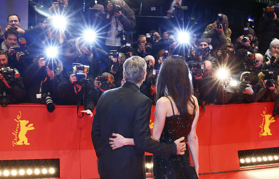 """US actor George Clooney, left, and his wife Amal Clooney arrive at the red carpet for """"Hail, Caesar!"""" the opening film of the 2016 Berlinale Film Festival in Berlin, Germany, Thursday, Feb. 11, 2016. (AP Photo/Axel Schmidt)"""