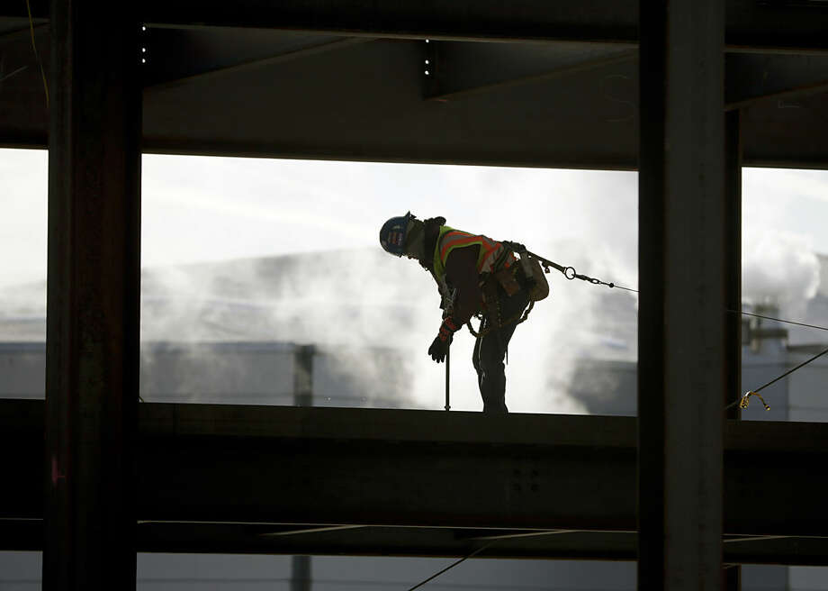 A worker braves cold temperatures while working atop steel beams at the Albany convention center project on Friday, Feb. 12, 2016, in Albany, N.Y. The National Weather Service has issued lake-effect snow warnings that remain in effect until late Friday night for western New York and into early Saturday for northern New York, while wind chill warnings are in effect for most of the upstate region through the weekend. (AP Photo/Mike Groll)