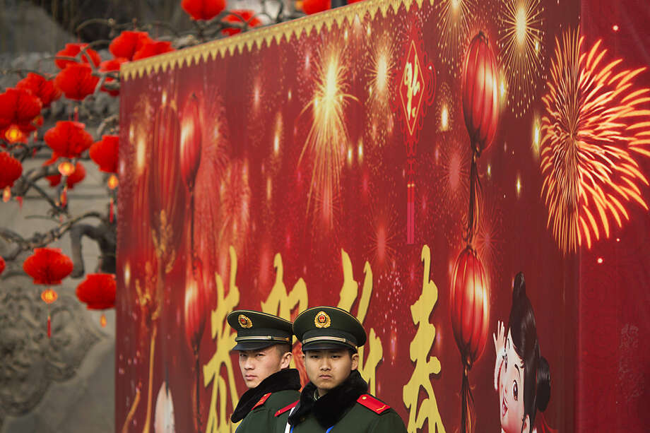 Chinese paramilitary policemen stand on duty outside a temple fair held during the Spring Festival holidays in Beijing, China, Friday, Feb. 12, 2016. The new year marks the Year of the Monkey and hundreds of thousands of residents in the Chinese capital visited traditional fairs held in parks, as well as Buddhist and Taoist temples offering singing and dance performances as well as open-air markets selling handicrafts and food. (AP Photo/Ng Han Guan)