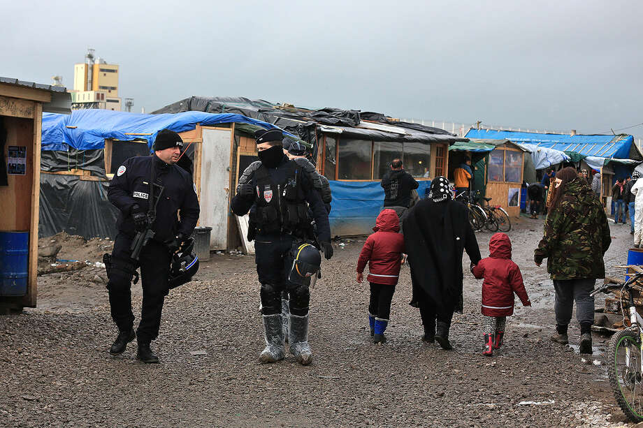 In this Feb. 5, 2016 photo, French riot police officers patrol in the migrant camp in Calais, north of France. Mysterious armed groups are on the prowl, targeting migrants in night attacks in Calais and other migrant haunts in northern France, sowing fear among the displaced travelers living in squalid slums in hopes of sneaking into Britain but also deepening concerns Calais is becoming a tinderbox fueled with anti-migrant rage and a breeding ground for nationalists. (AP Photo/Thibault Camus)
