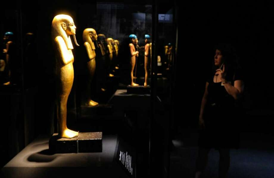 "NEW YORK - APRIL 21:  A woman looks at objects on display during the press preview of the ""Tutankhamun And The Golden Age Of The Pharaohs"" exhibition at the Discovery Times Square Exposition Center on April 21, 2010 in New York City.  (Photo by Jemal Countess/Getty Images) Photo: Jemal Countess, Getty Images / 2010 Getty Images"