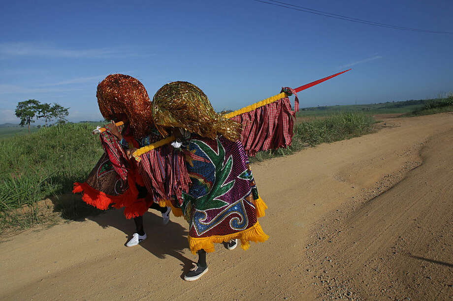 "In this Feb. 7, 2016 photo, ""Caboclo de Lanca,"" or lance-bearers, Nego Benvindo, left, and Jose Esteves, walk to town for Maracatu Carnival celebrations in Nazare da Mata, Brazil. The Afro-indigenous tradition is one of the oldest in northeastern Pernambuco state. (AP Photo/Eraldo Peres)"