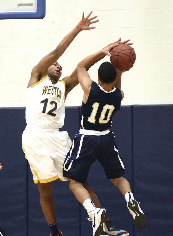 Hour photo/John NashWeston's Nik Parker (12) looks to challenge Immaculate's Darrius Smith on a shot.