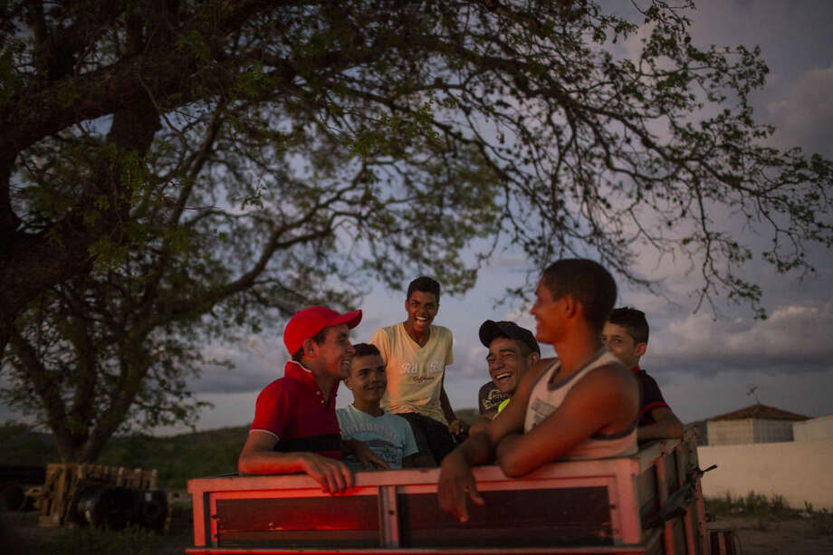 Boys joke as they ride on a cart being pulled by a car in Albuquerque, Pernambuco state, Brazil, Sunday, Feb. 7, 2016. The South American country has been the hardest hit by Zika virus, and the northeastern state of Pernambuco, is the epicenter of the Zika outbreak. (AP Photo/Felipe Dana)