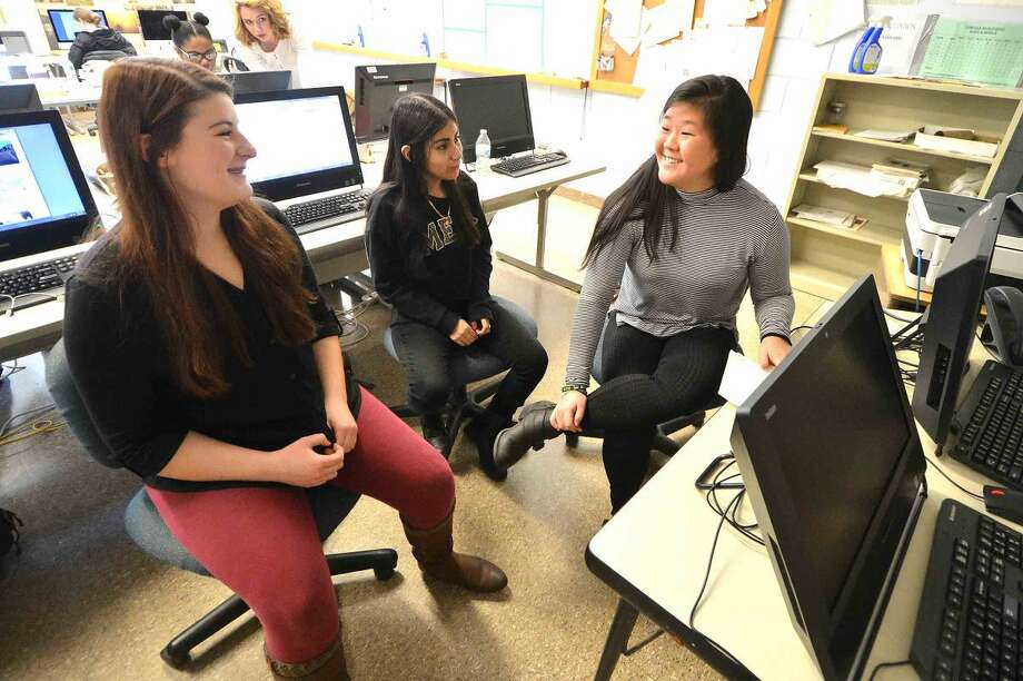 Hour Photo/Alex von Kleydorff Norwalk High School Journalism students Sports Editor Hannah Keyes, Reporter Maria Saldana and Arts and Life Co Editor Jannalee Potmesil discuss the next issue of the schools newspaper The Paw Print during Journalism class