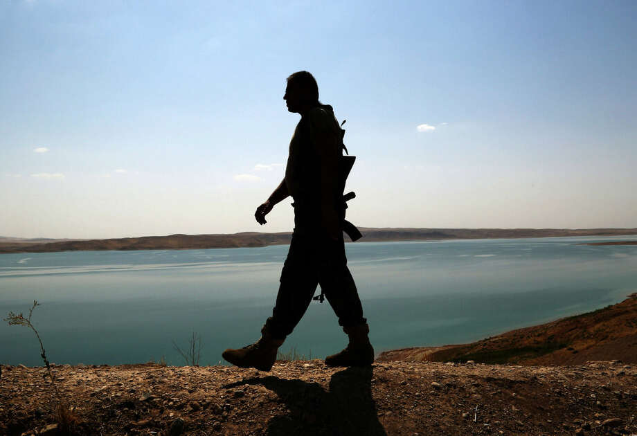 FILE -- In this Aug. 17, 2014 file photo, a Kurdish peshmerga fighter patrols near the Mosul Dam at the town of Chamibarakat outside Mosul, Iraq. An Italian engineering firm is set to ink a contract with the Iraqi government to begin shoring up the country's rickety Mosul dam. But engineering experts warn the rehabilitation plans are nowhere near a solution and that the key piece of Iraqi infrastructure is beyond repair. (AP Photo/Khalid Mohammed, File)