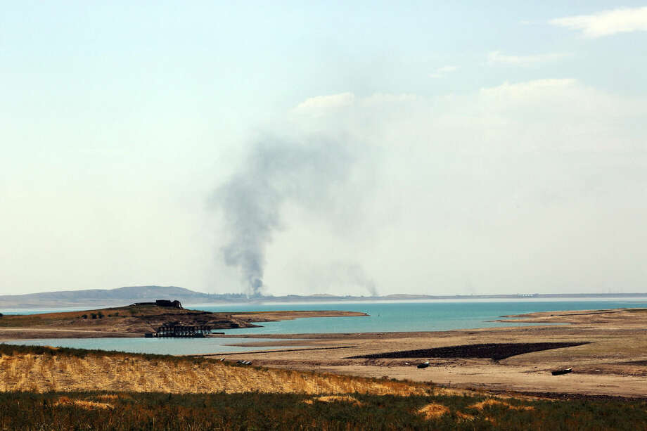 FILE - In this Aug. 18, 2014 file photo, smoke rises during airstrikes targeting Islamic State militants at the Mosul Dam outside Mosul, Iraq. An Italian engineering firm is set to ink a contract with the Iraqi government to begin shoring up the country's rickety Mosul dam. But engineering experts warn the rehabilitation plans are nowhere near a solution and that the key piece of Iraqi infrastructure is beyond repair. (AP Photo/ Khalid Mohammed, File)