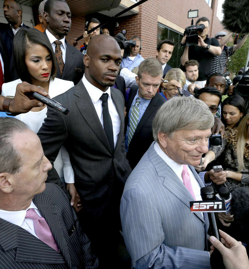 ADVANCE FOR WEEKEND EDITION, JAN. 31-FEB. 1 - FILE - In this Oct. 8, 2014, file photo, Minnesota Vikings running back Adrian Peterson, center, stands with his wife Ashley Brown Peterson, left, as they listen to Peterson's attorney Rusty Hardin, right, outside the courthouse after making his first court appearance in Conroe, Texas. Concussions, domestic abuse arrests, questionable officiating and another cheating controversy. And yet, the league still popular as ever with ratings and revenue streams that make other leagues jealous. (AP Photo/David J. Phillip, File)