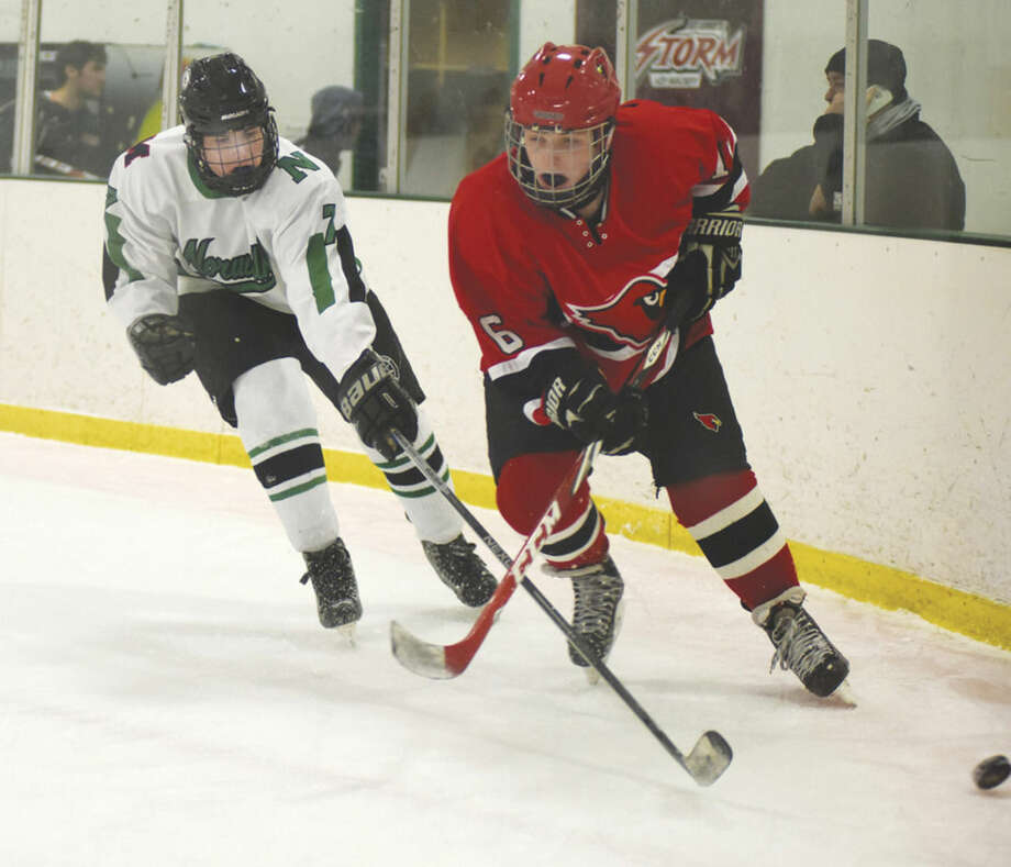 Hour photo/John NashNorwalk-Brien McMahon's Will Haskell, left, poke-checks a puck from a Greenwich player as the co-op team hosted the Cardinals on its Senior Night at the SoNo Ice House.