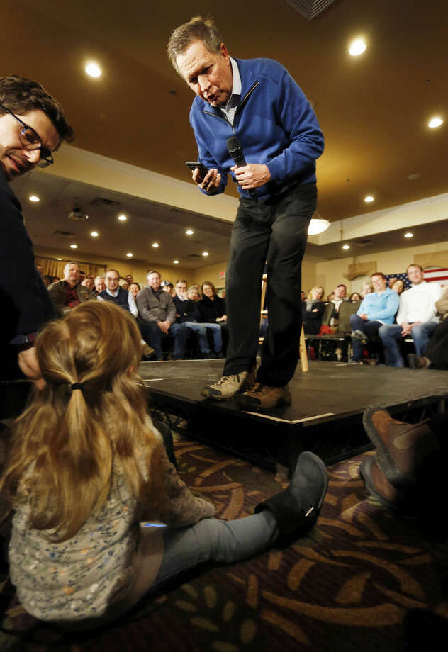 Republican presidential candidate Ohio Gov. John Kasich talks to Logan Peschiera during his last town hall before Tuesday's first in the nation presidential primary Monday, Feb. 8, 2016, in Manchester, N.H. (AP Photo/Jim Cole)